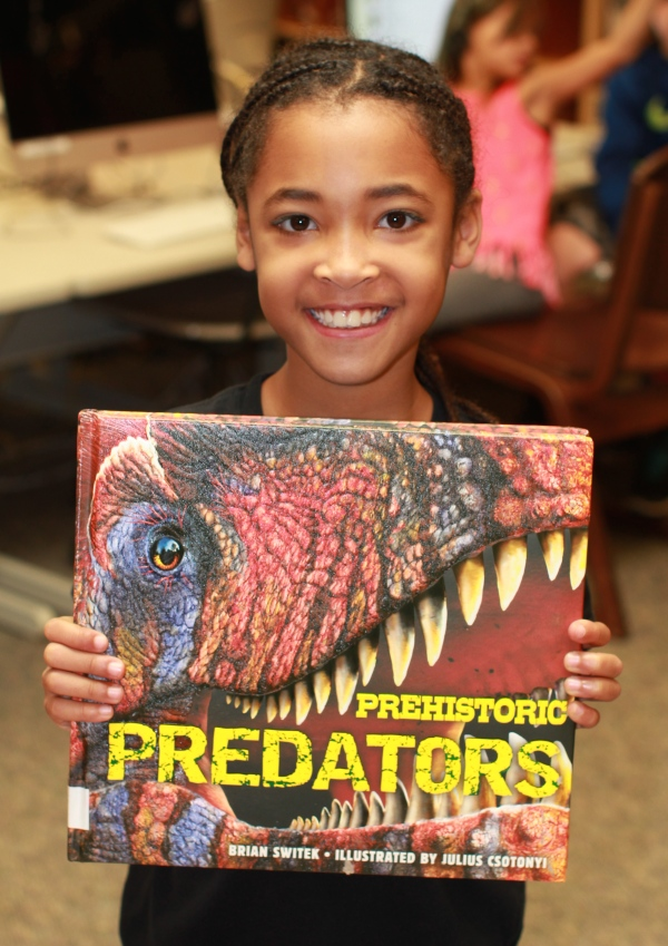 "Donors Choose Book ""Prehistoric Predators"" held by girl"
