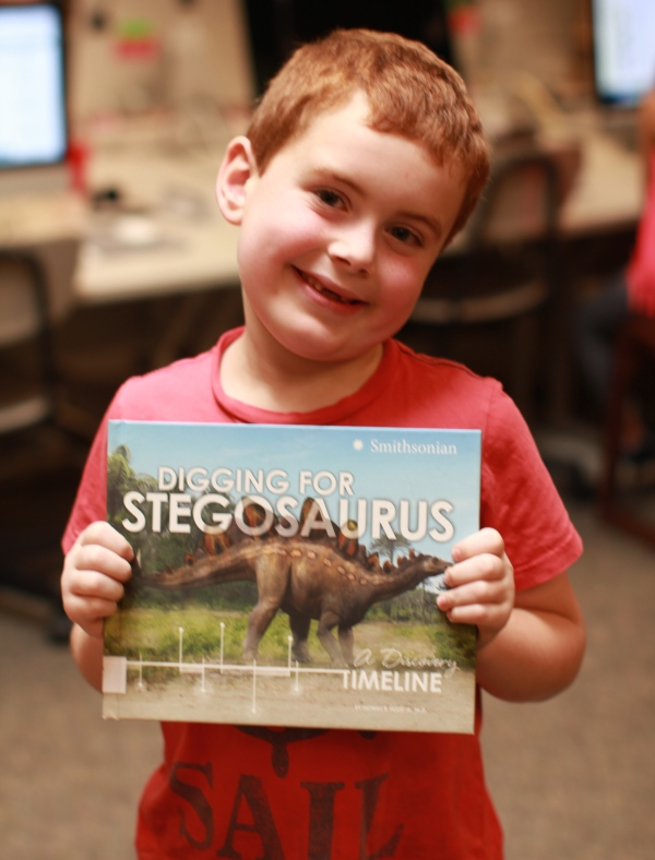 "Donors Choose Book ""Digging for Stegosaurus"" held by boy"
