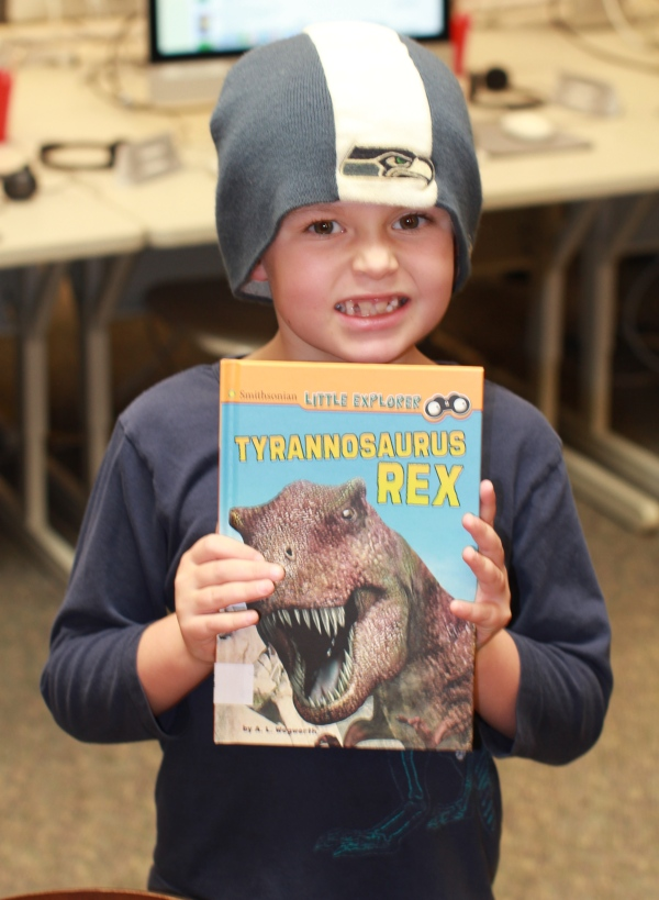 "Donors Choose Book ""Tyrannosaurus Rex"" held by girl"