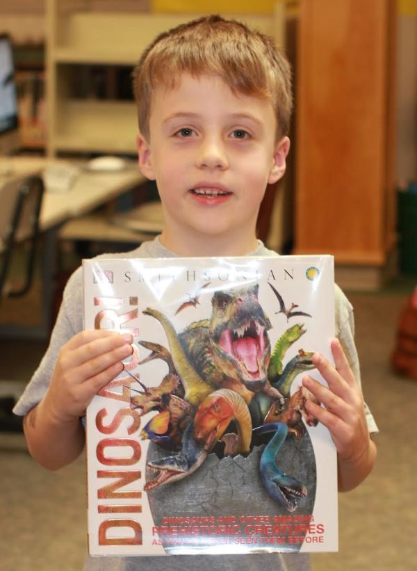 "Donors Choose Book ""Dinosaurs"" held by boy"