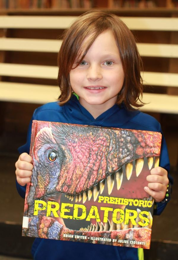 "Donors Choose Book ""Prehistoric Predators"" held by boy"