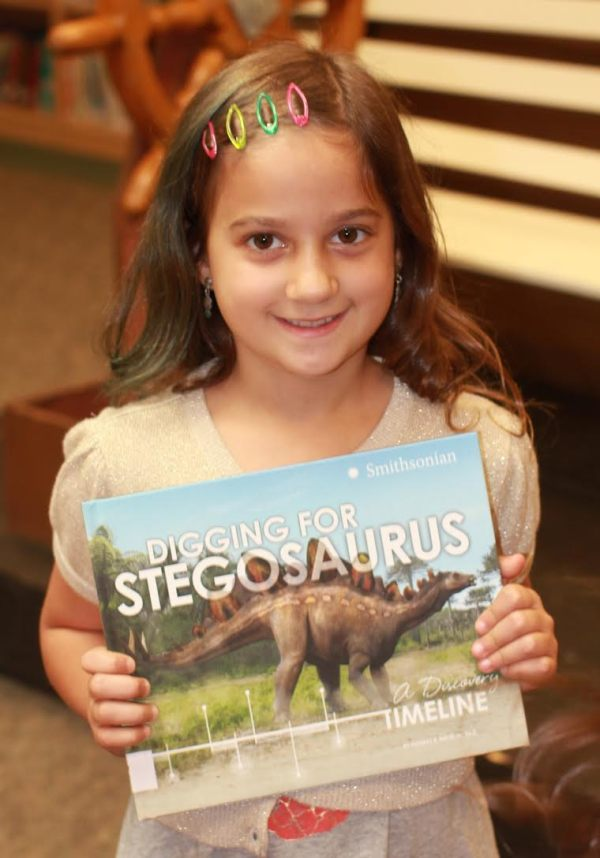 "Donors Choose Book ""Digging For Stegosaurus"" held by girl"