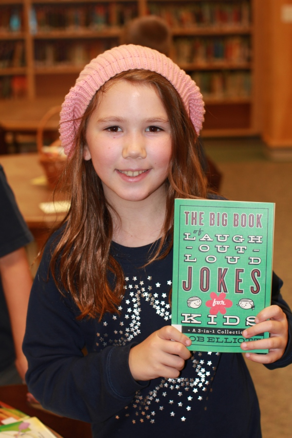 "Donors Choose Book ""The Big Book of Laugh out Loud Jokes For Kids"" held by girl"