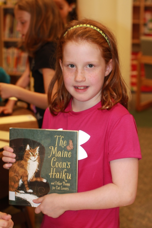 "Donors Choose Book ""The Maine Coon's Haiku"" held by girl"