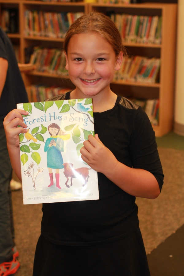 "Donors Choose Book ""Forest Has a Song"" held by girl"