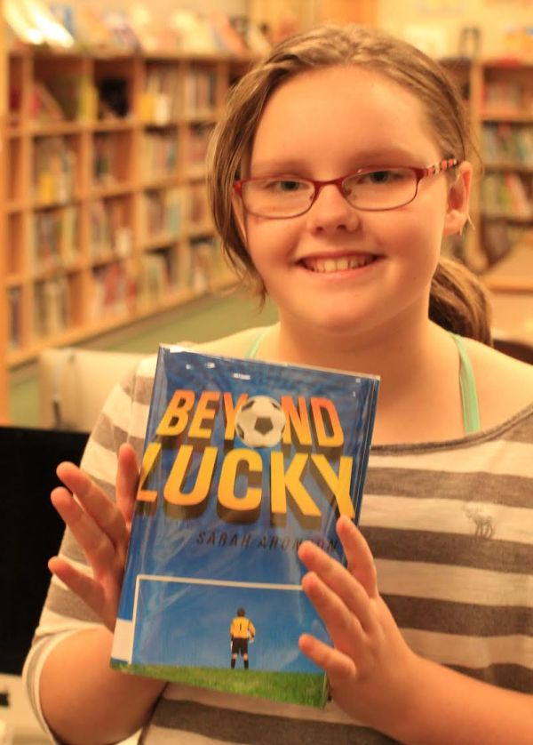 "Donors Choose Book ""Beyond Lucky"" held by girl"