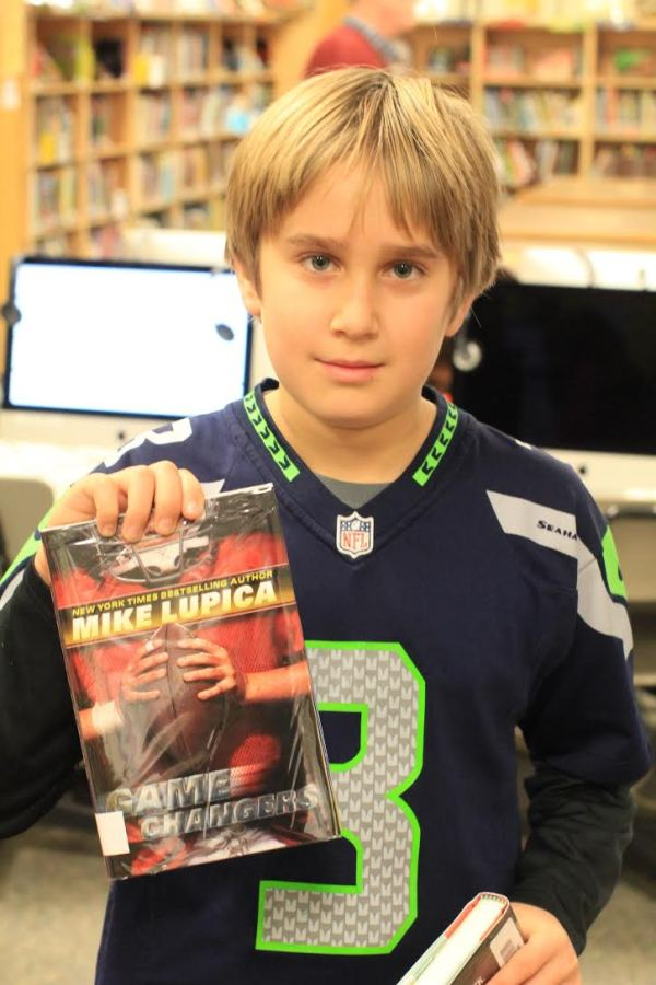 "Donors Choose Book ""Game Changers"" held by boy"