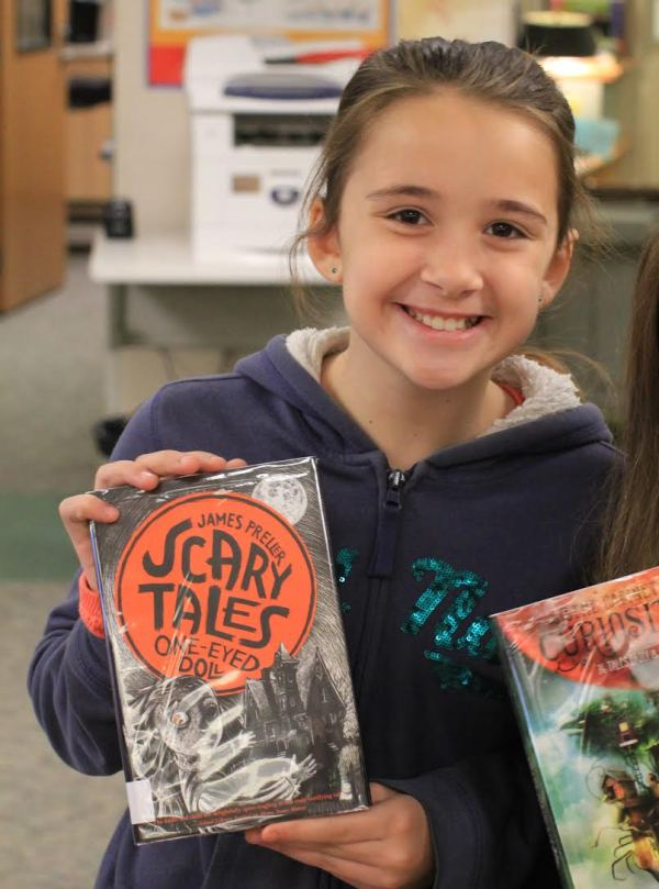 "Donors Choose Book ""Scary Tales: One-Eyed Doll"" held by girl"