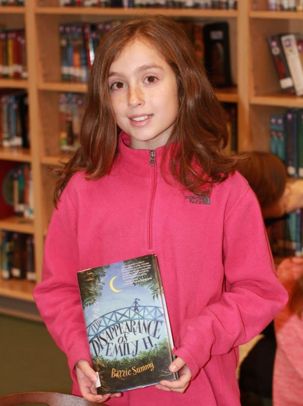 """Donors Choose Book """"Disappearance of Emily H"""" held by girl"""