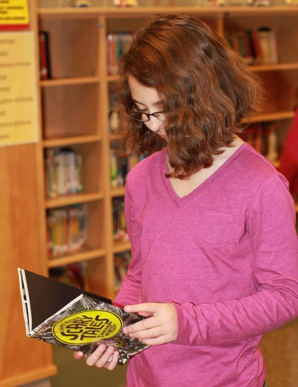 """Donors Choose Book """"Scary Tales Swamp"""""""" held by girl"""