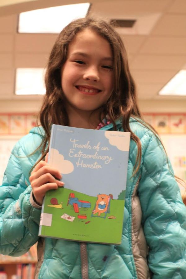 "Donors Choose Book ""Travels of an Extraordinary Hamster"" held by girl"