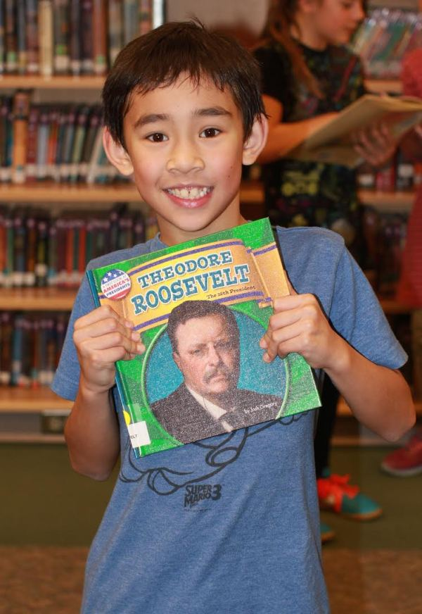 "Donors Choose Book ""Theodore Roosevelt"" held by boy"