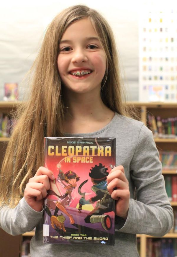 "Donors Choose Book ""Cleopatra In Space"" held by girl"