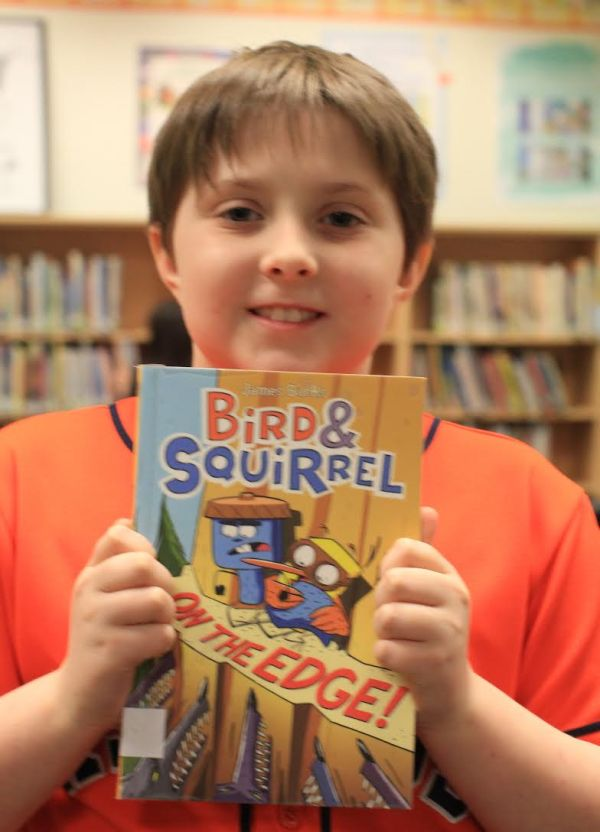 "Donors Choose Book ""Bird & Squirrel On The Edge"" held by girl"