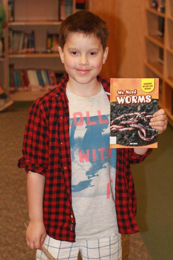 "Donors Choose Book, Boy holding ""We Need Worms"""
