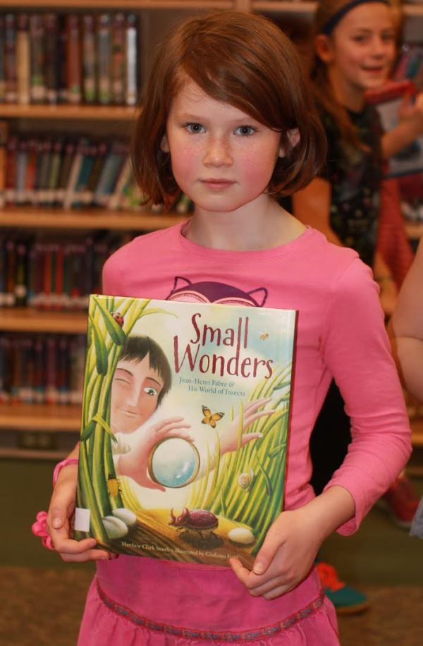 "Donors Choose Book ""Small Wonders"" held by girl"